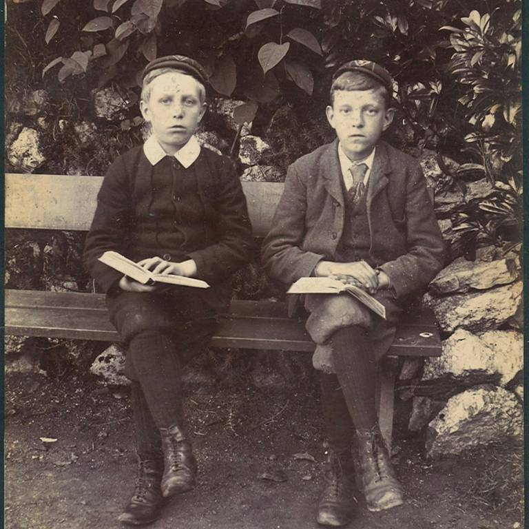 Two boys sat on bench reading
