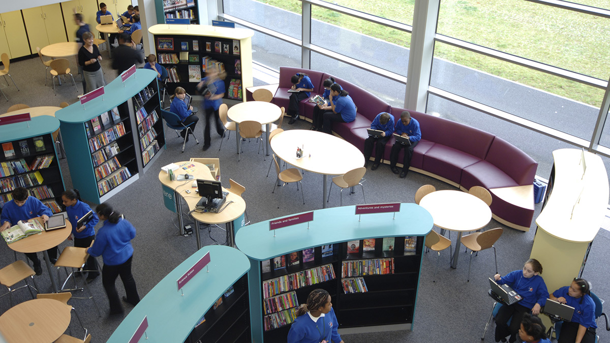 Pupils reading in school library interacting with shelves and seating