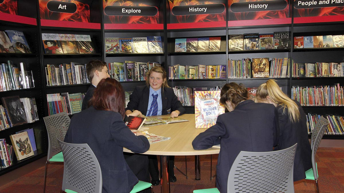 School pupils reading at school library study table