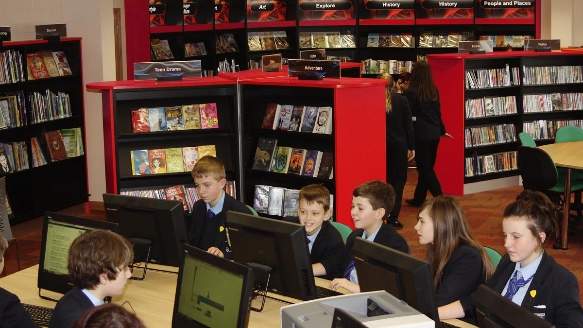 Children working at school library IT desk with bookcases in background