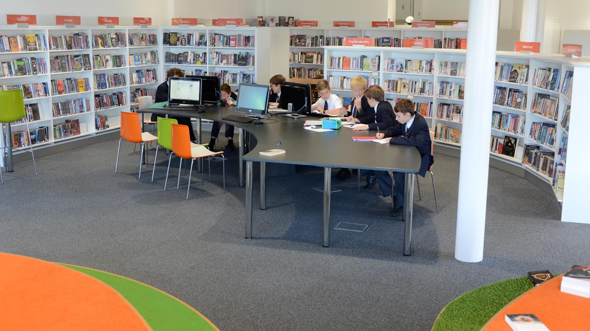 Children working at school library IT in newly designed and modern library
