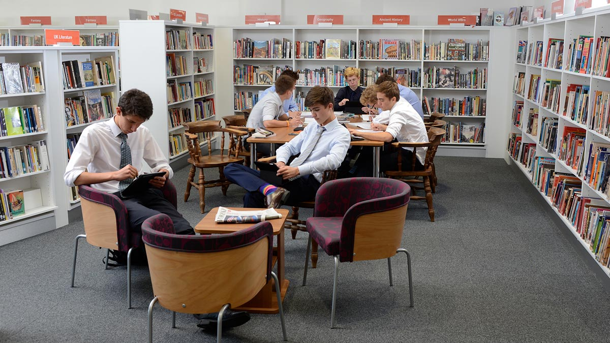 School pupils reading and studying in library seating area and at library study desk