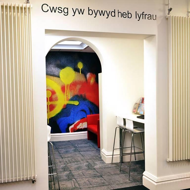 Urban-style flooring and graffiti graphic in teens' area, Llandudno Library